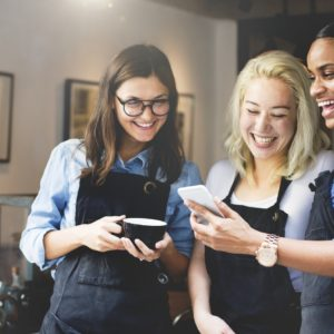 three employees read a message on a mobile device
