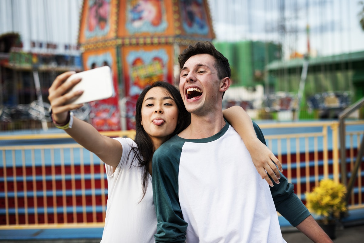 Two Gen Z individuals take a selfie with a smartphone